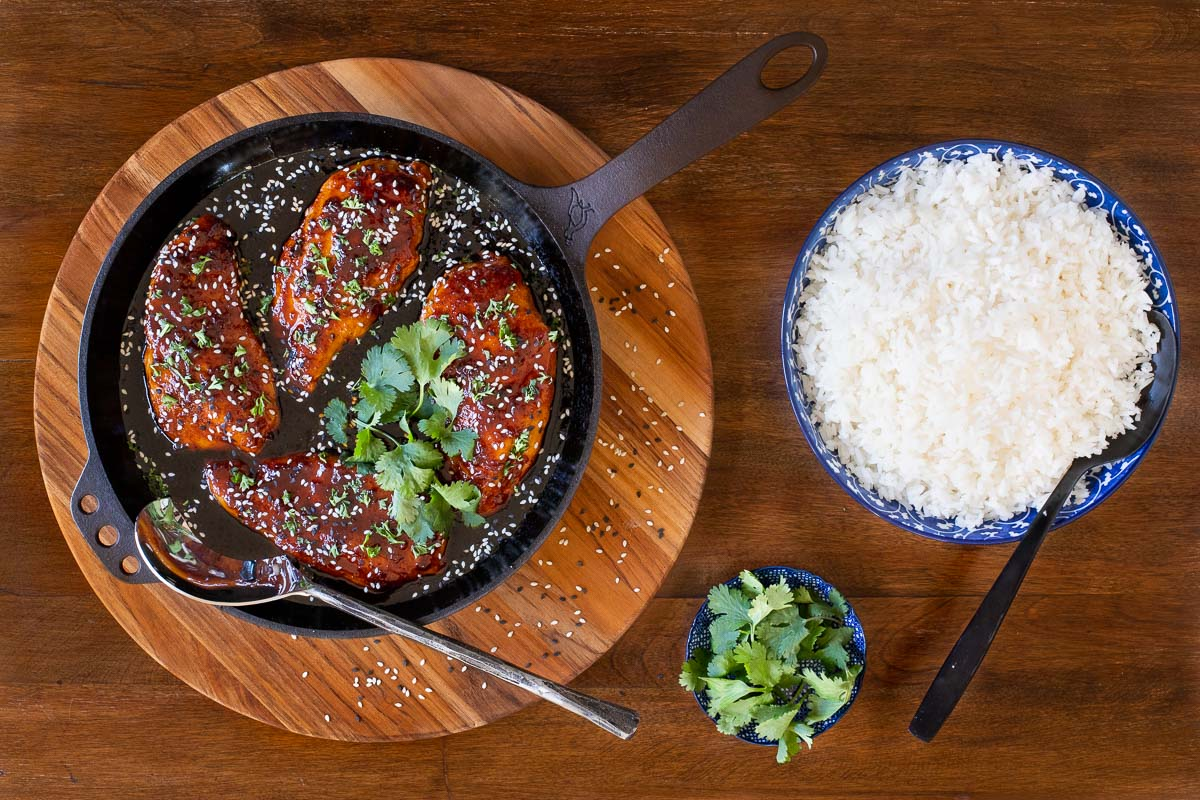 Horizontal overhead photo of Indonesian Sticky Ginger Chicken Breasts in a skillet surrounded by bowls of rice and fresh cilantro.