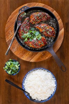 Vertical overhead photo of a skillet of Honey Ginger Indonesian Chicken surrounded by bowls of rice and fresh cilantro.