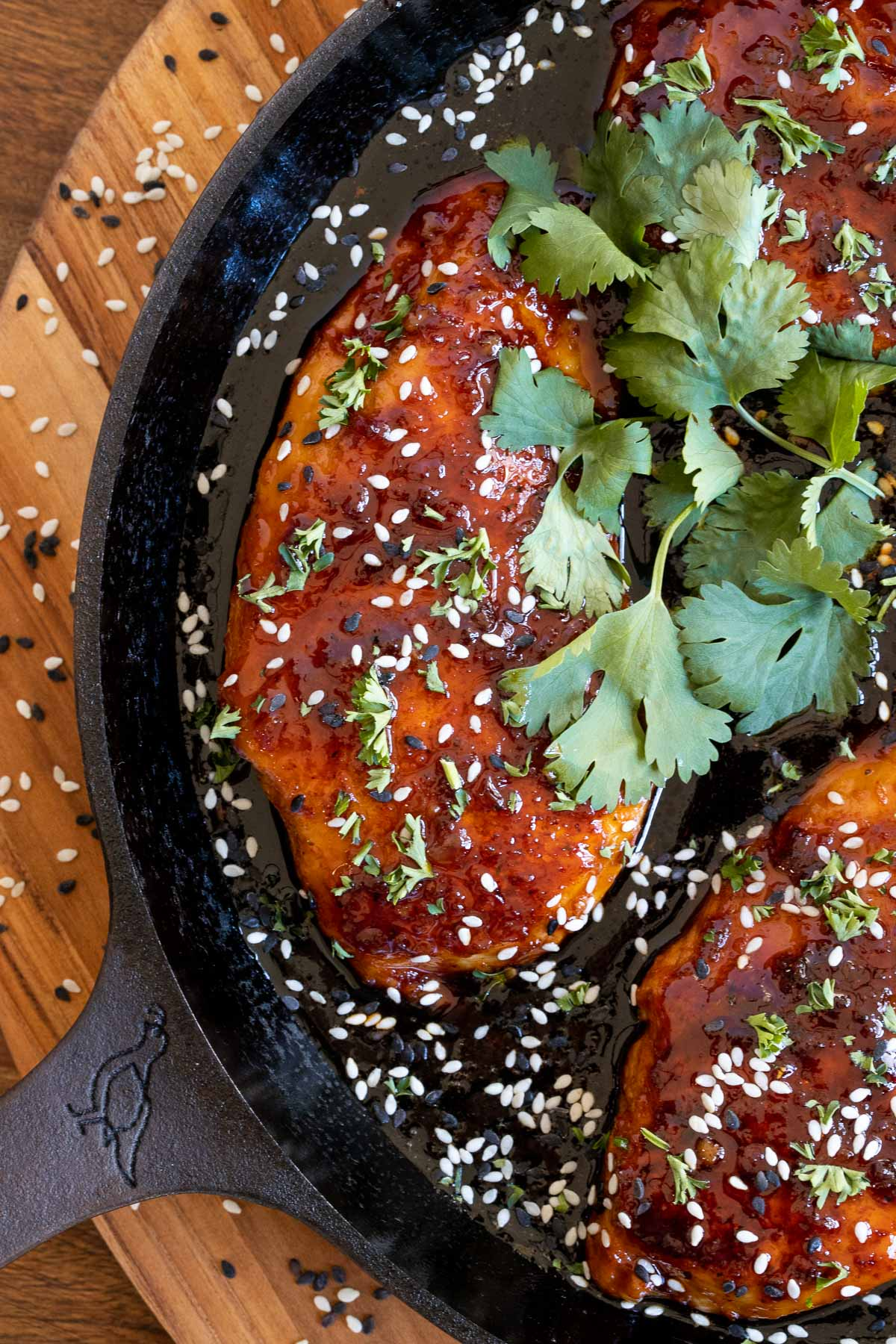 Overhead vertical closeup photo of Indonesian Sticky Ginger Chicken Breasts in a cast iron skillet garnished with fresh cilantro and tuxedo sesame seeds.