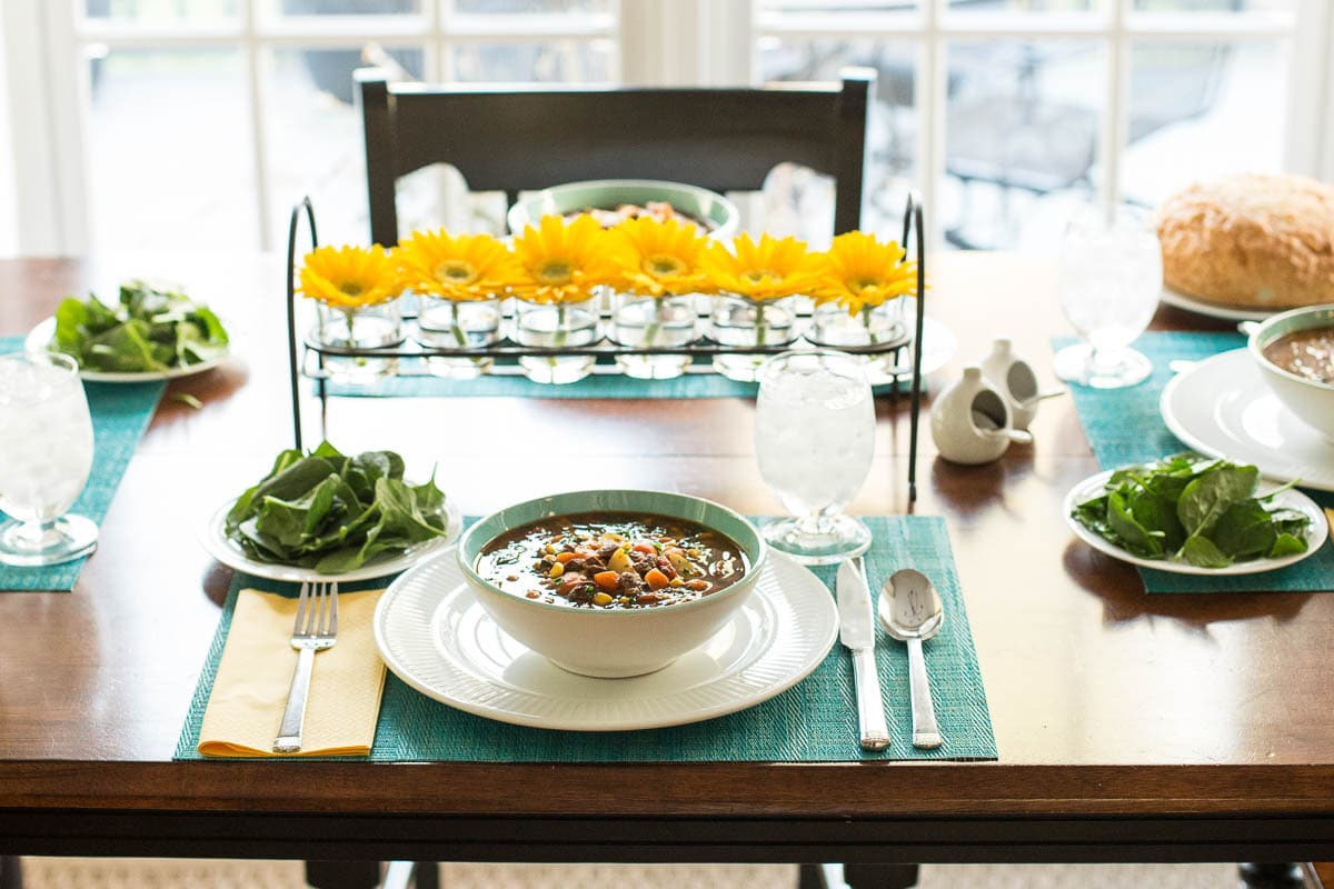 A dinner table setting featuring a bowls of Instant Pot Italian Vegetable Beef Soup.