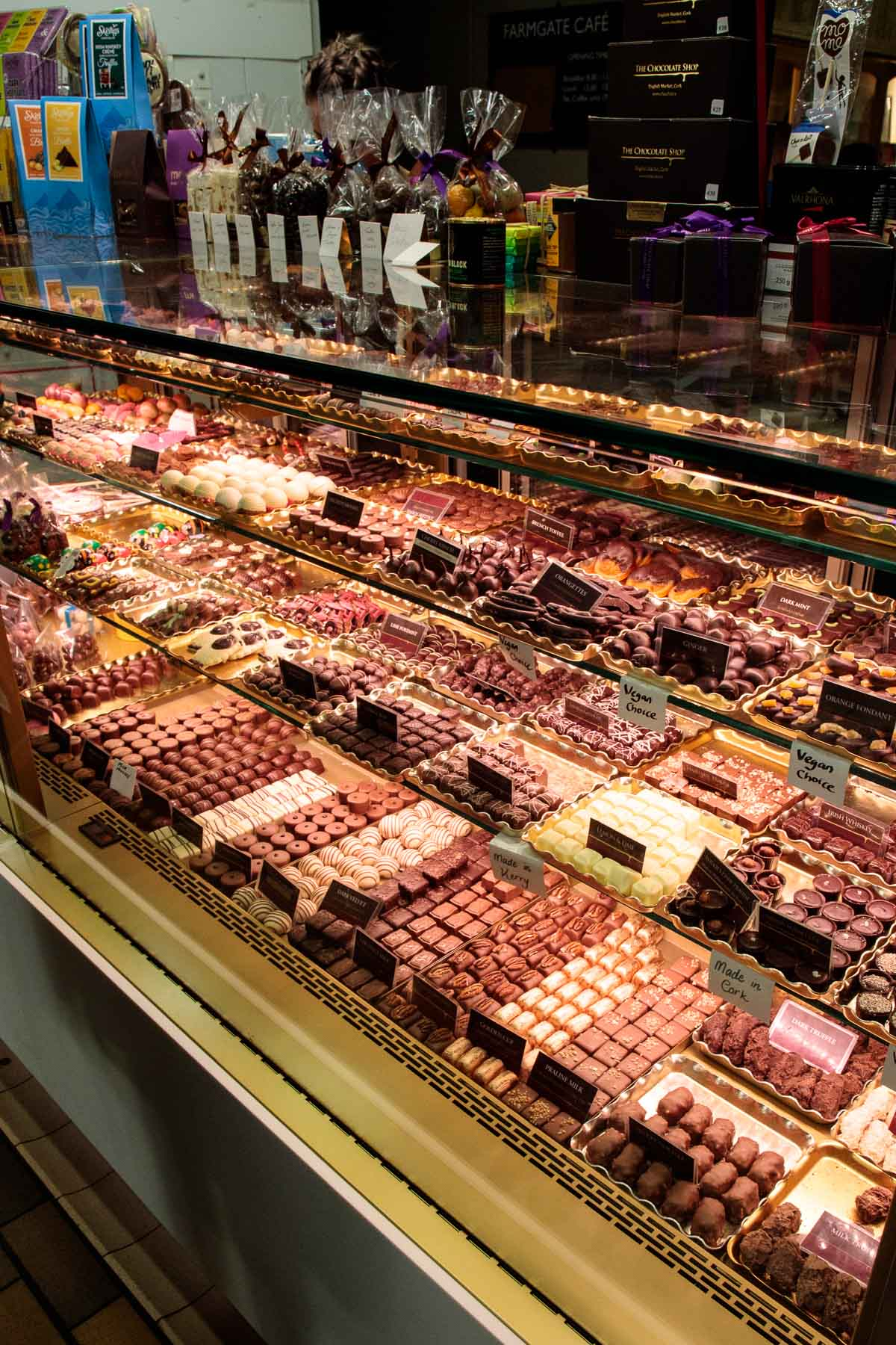 Photo of a nearly infinite display of hand made fine chocolates at the English Market in Cork, Ireland.