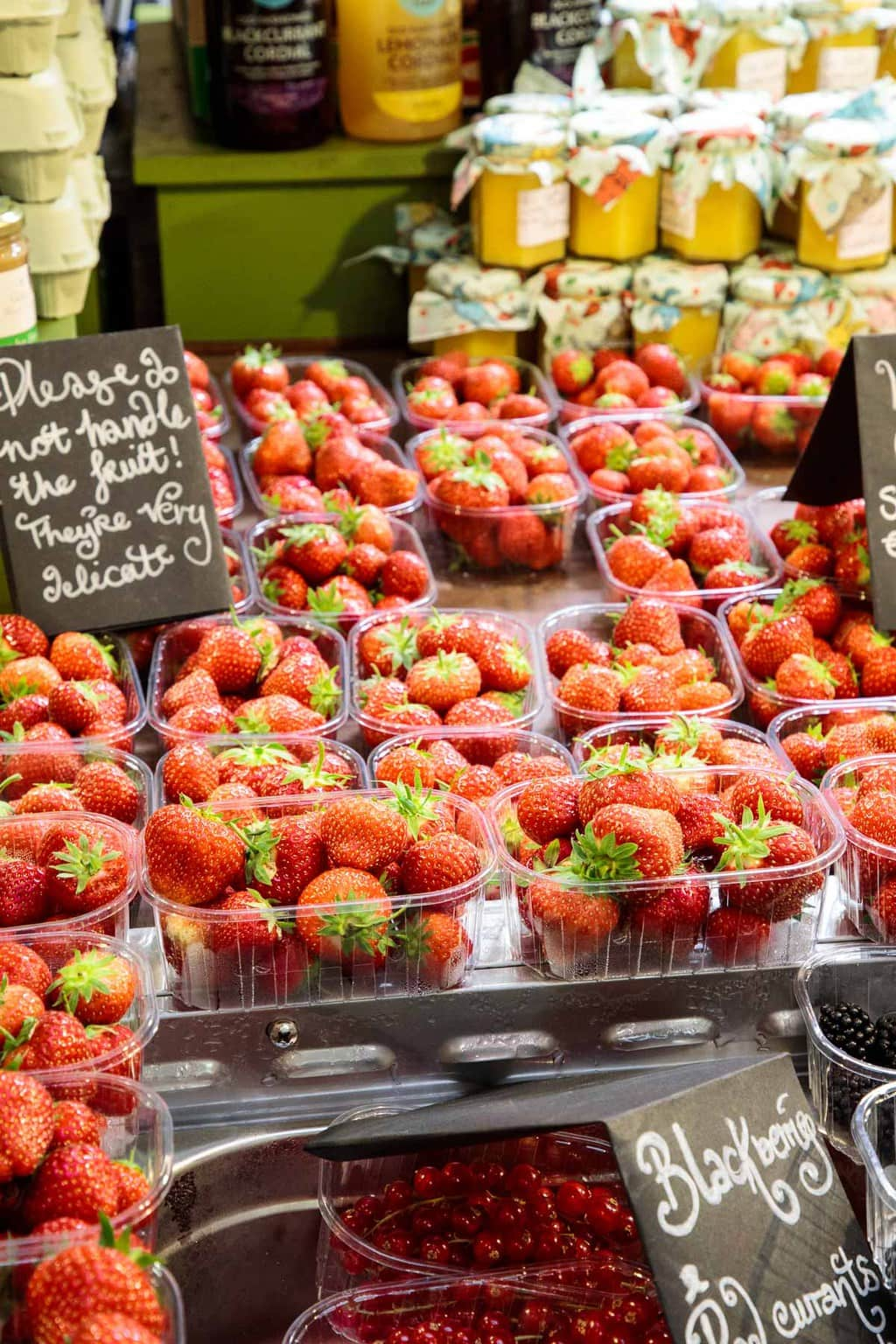 A photo of fresh picked strawberries in baskets for sale at the Cork English Market.