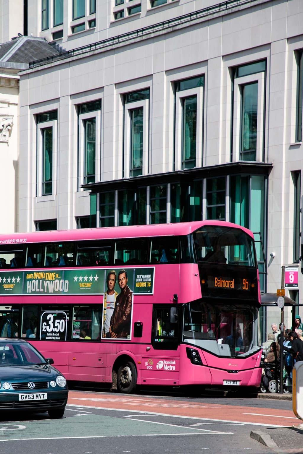 Photo of a Belfast hot pink double decker bus.