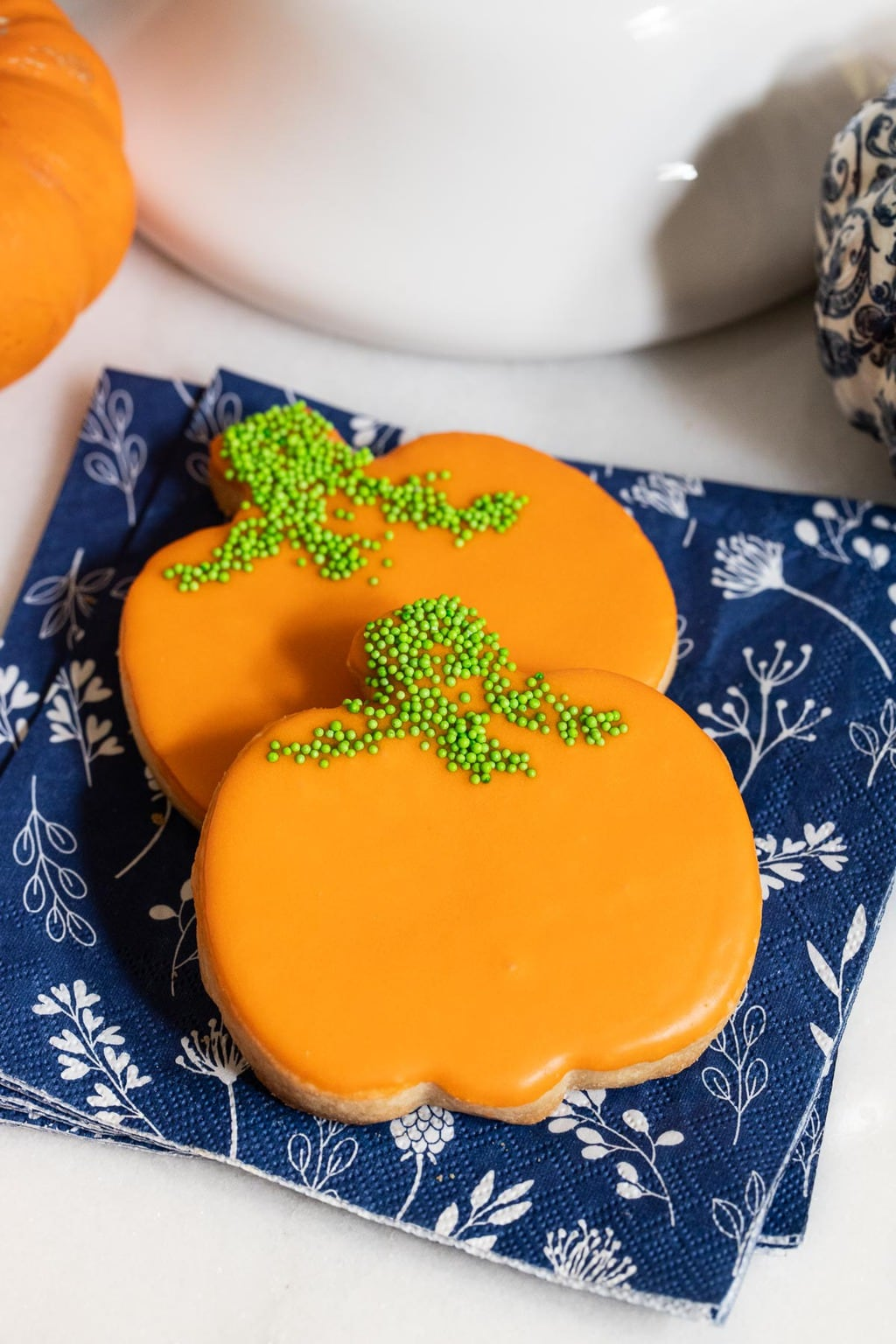 Vertical closeup photo of a pair of Irish Shortbread Pumpkin Patch Cookies on a navy and white patterned napkin.