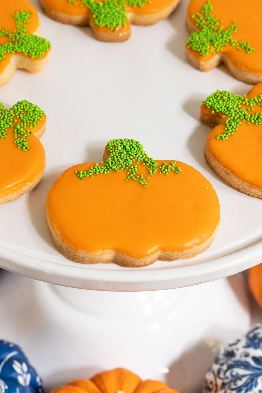 Vertical closeup photo of Irish Shortbread Pumpkin Patch Cookies on a white pedestal cake stand.
