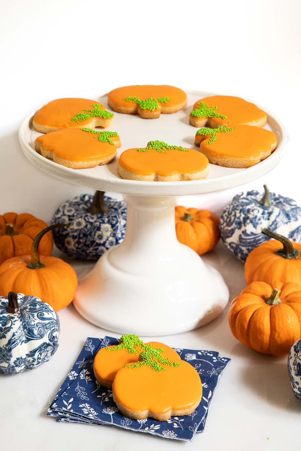Vertical photo of a batch of Irish Shortbread Pumpkin Patch Cookies on and around a white pedestal serving stand.