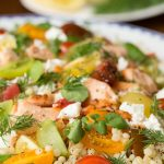 Closeup Vertical image of Israeli Couscous Salmon Salad on a blue and white platter.