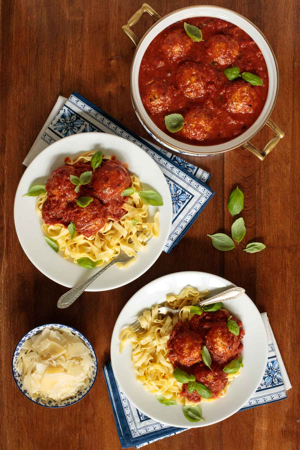 Overhead photo of a pot and two serving bowls of Italian Chicken Meatballs and Marinara with pasta and shaved Parmesan cheese.
