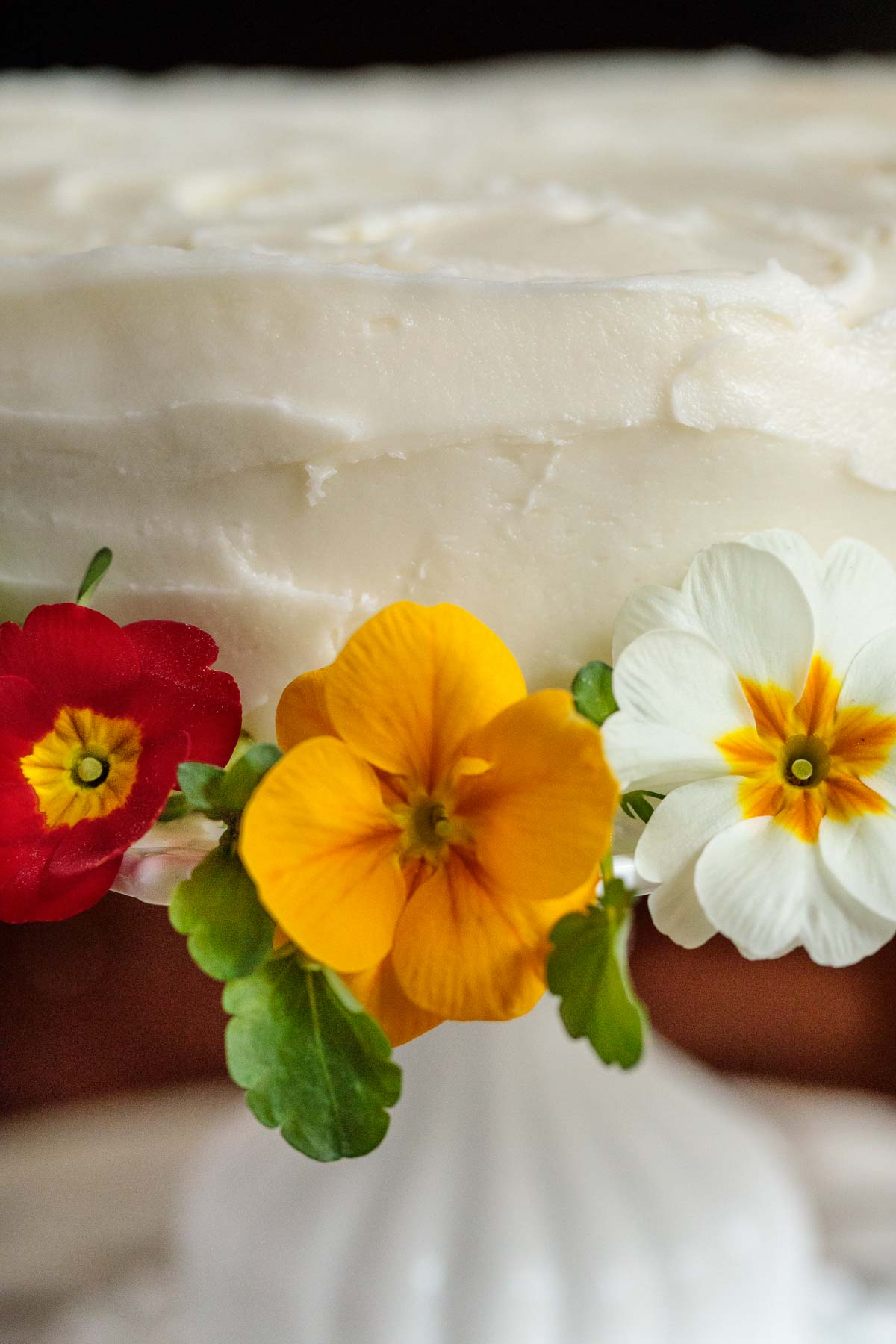 Ultra closeup photo of edible flowers (pansies and primroses) decorating the side of an Italian Lemon Ricotta Cake.