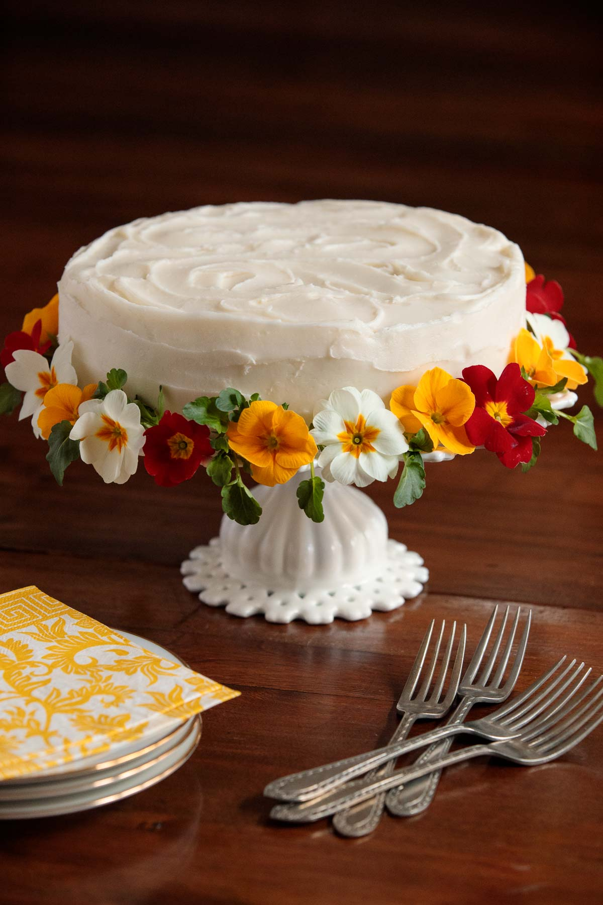 Table photo of an Italian Lemon Ricotta Cake on a white pedestal cake platter, surrounded by pansies and primroses with serving utensils and plates in the foreground.