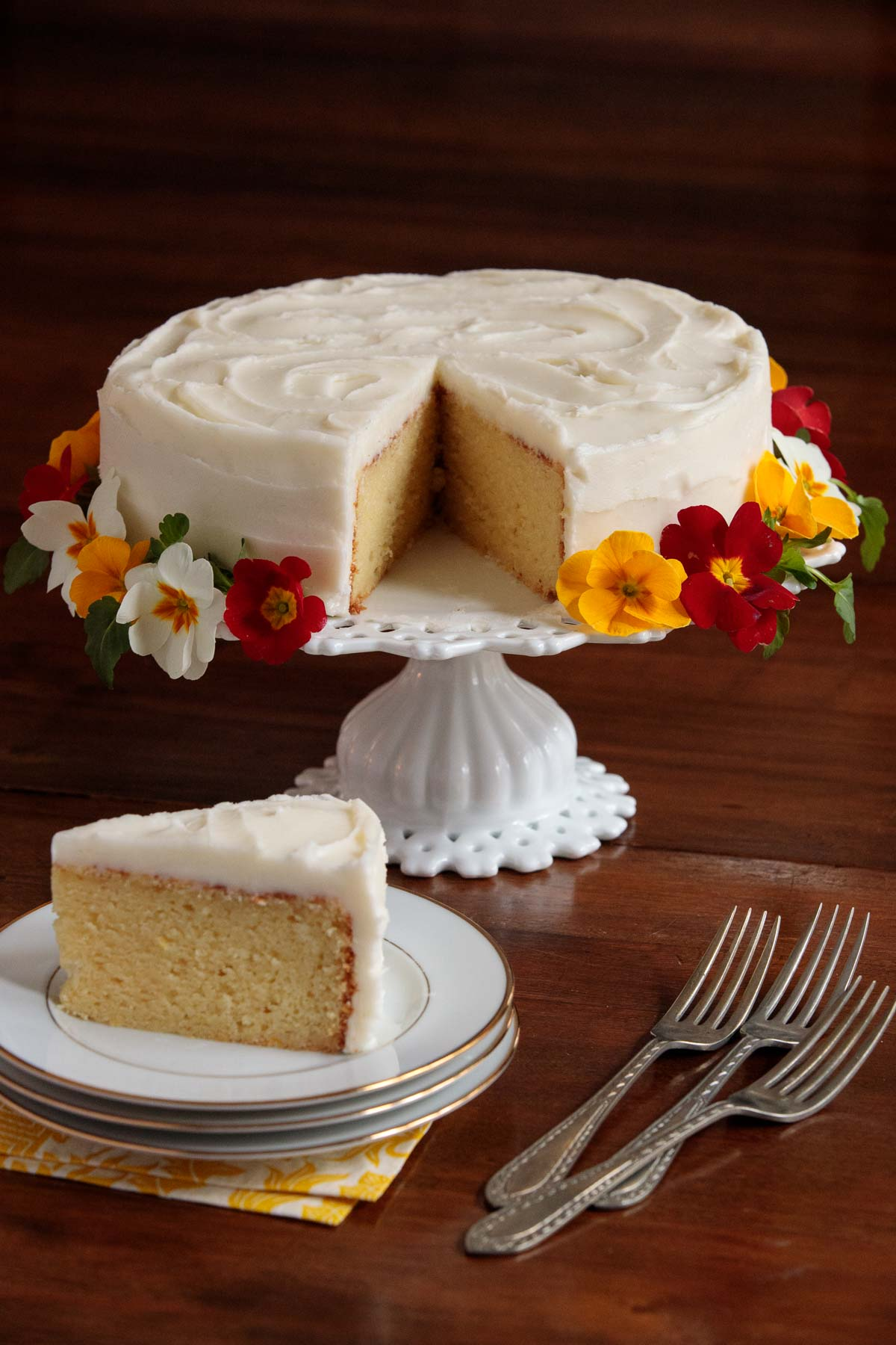 Photo of an Italian Lemon Ricotta Cake with a slice removed and on a separate serving plate. The cake is banded by pansies and primroses.