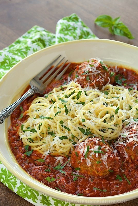 Overhead photo of Italian Meatballs and Marinara in a white bowl with a green and white patterned napkin.