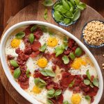 Overhead picture of Italian Polenta Breakfast Casserole in a white dish with toppings in small bowls