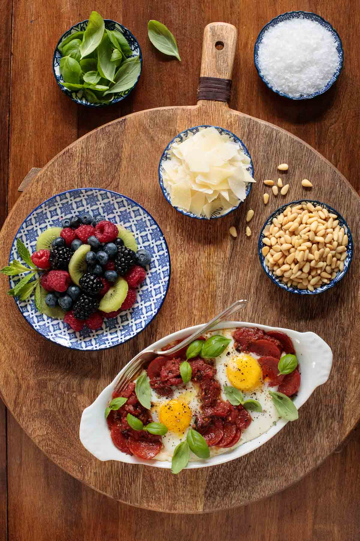 Overhead photo of an individual baking dish of Italian Polenta Breakfast Casserole on a round wood lazy Susan tray with Parmesan cheese shavings, pine nuts and a plate of fresh fruit nearby.