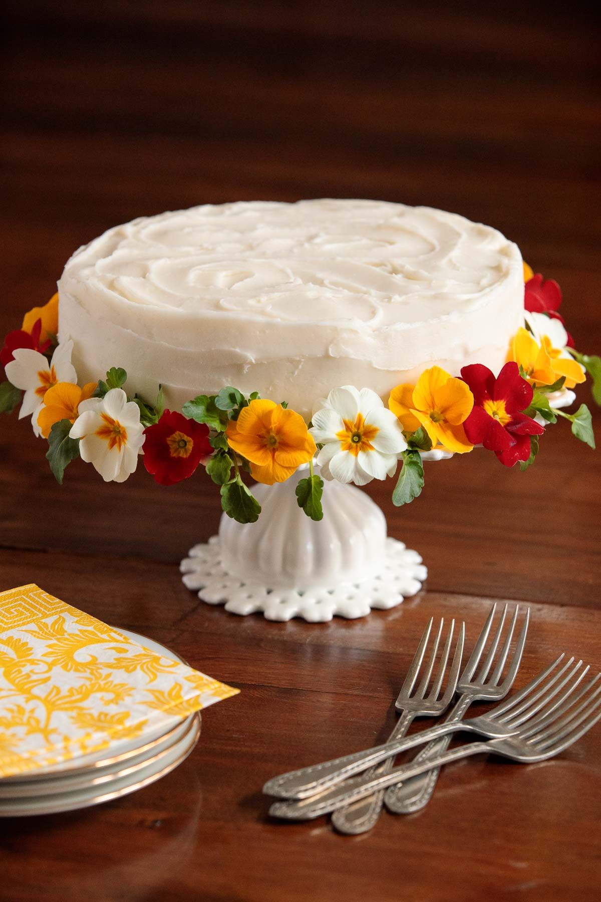 Vertical picture of Italian ricotta cake garnished with flowers on a white cake stand