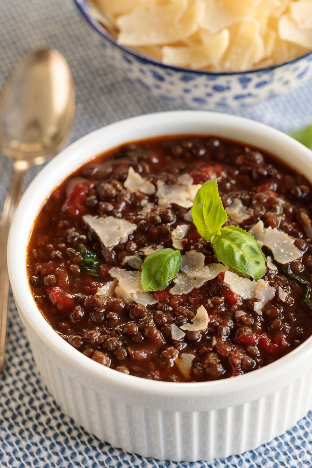 Vertical close up photo of Italian Sausage Black Lentil Soup in a small serving white bowl.