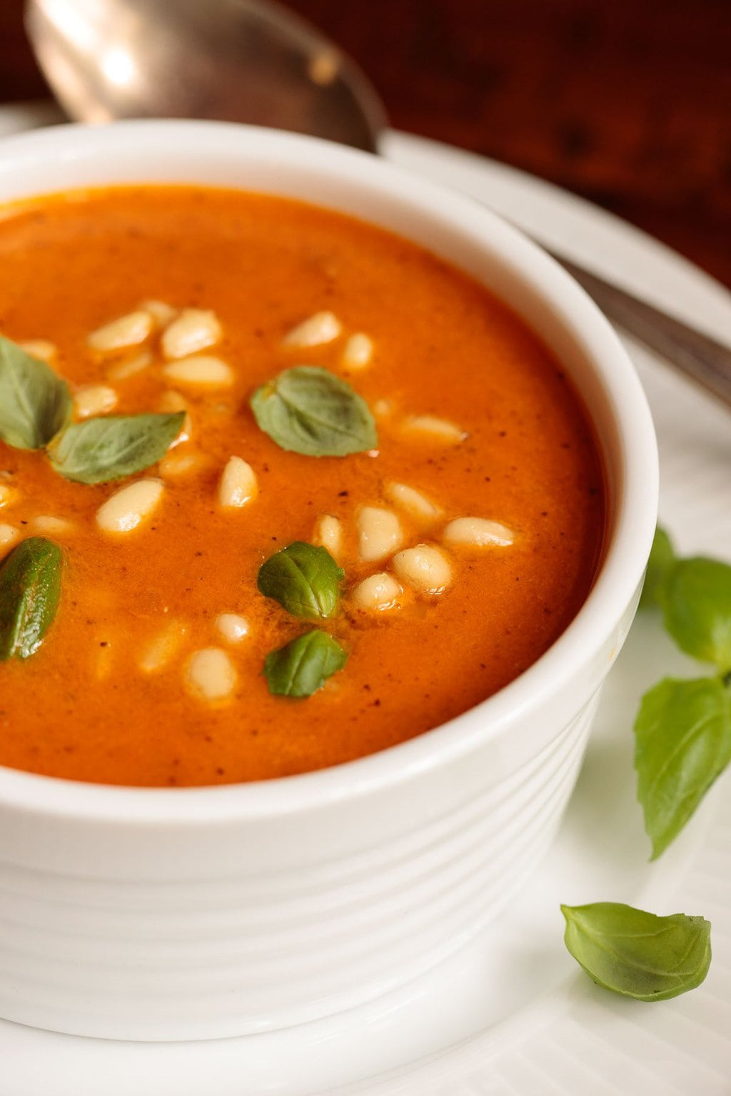 Photo of a white porcelain bowl filled with Italian Sun Dried Tomato Soup garnished with fresh basil leaves.