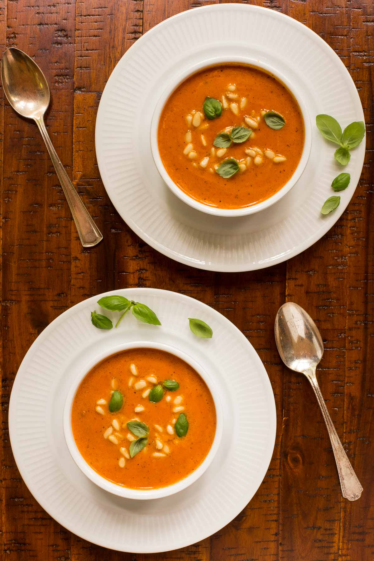 Overhead photo of two white serving bowls of Italian Sun Dried Tomato Soup on a wood table.