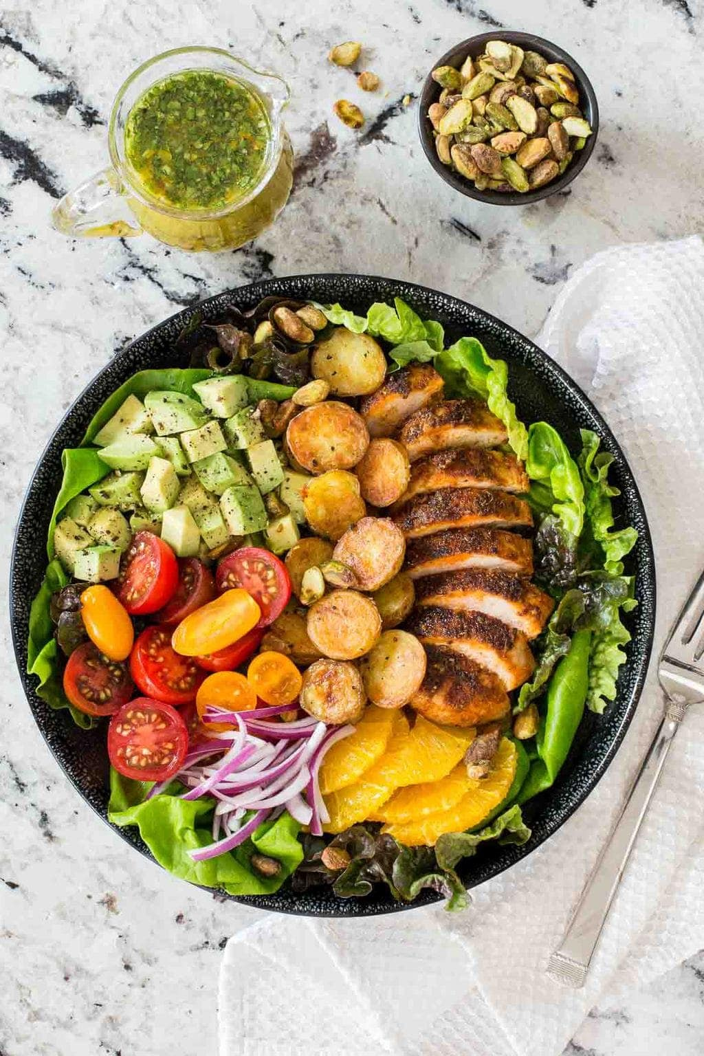 Vertical image of a salad with juicy tender chicken breasts in a black bowl on a granite surface.