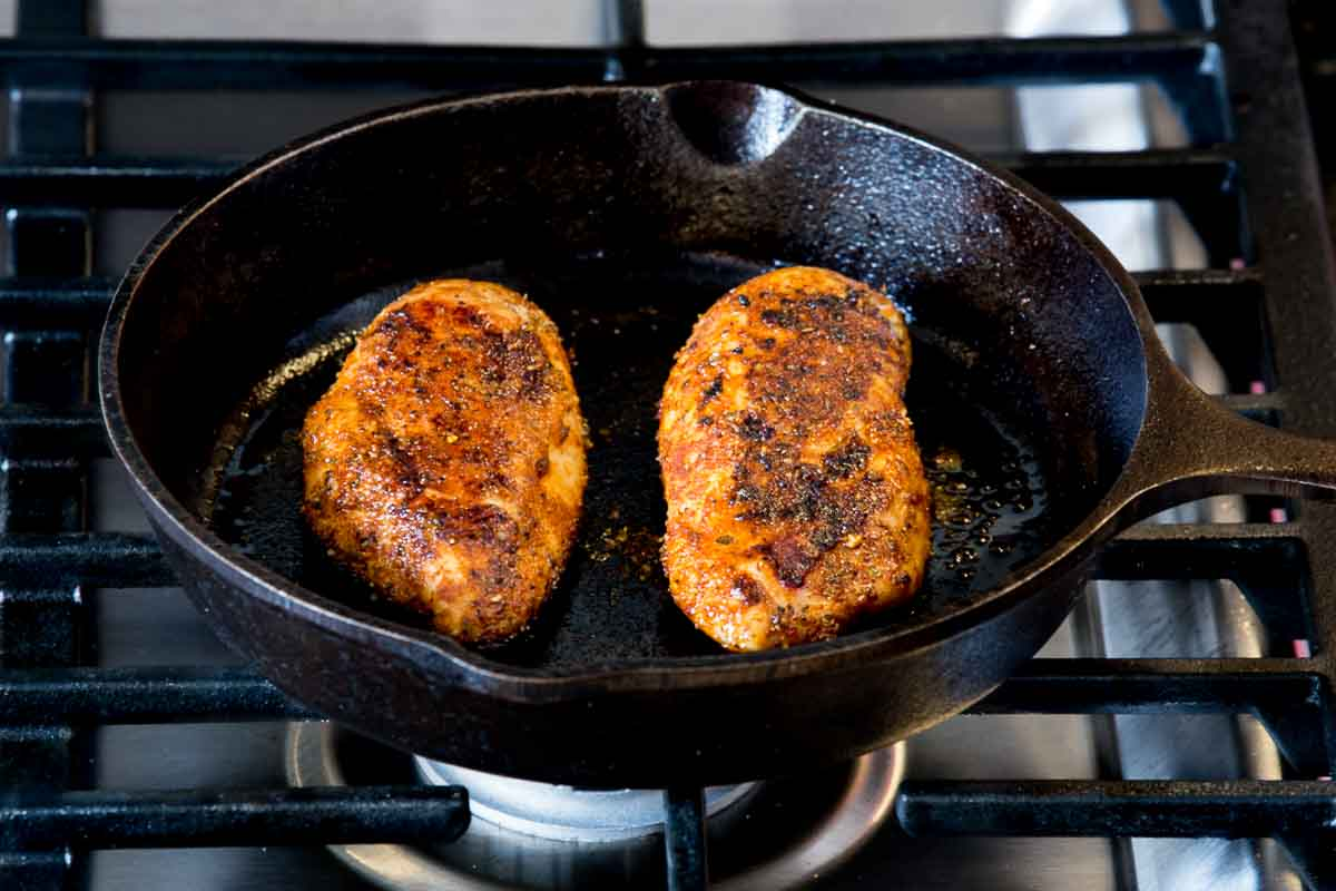 Horizontal photo of Juicy Tender Restaurant Style Chicken Breasts being cooked in a cast iron skillet on a gas stove top.