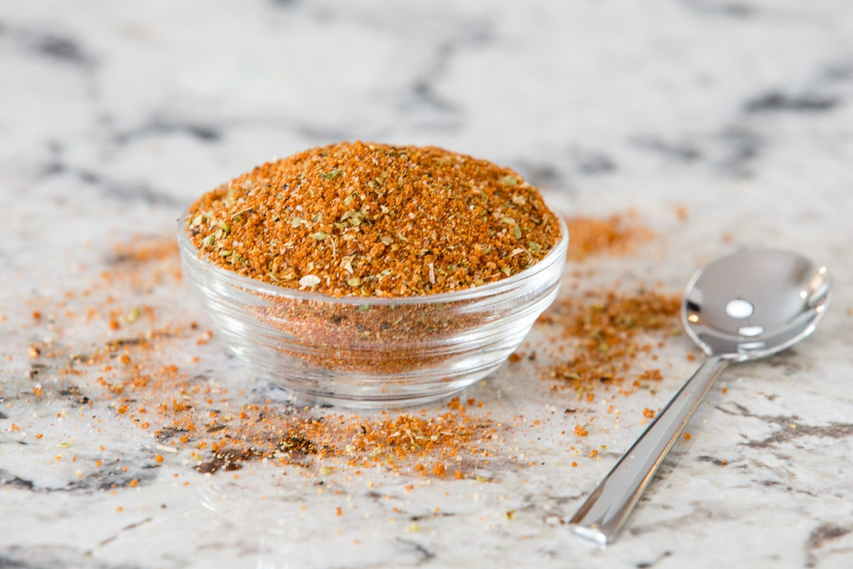 Horizontal closeup photo of a glass dish of rub for making Juicy Tender Restaurant Style Chicken Breasts.