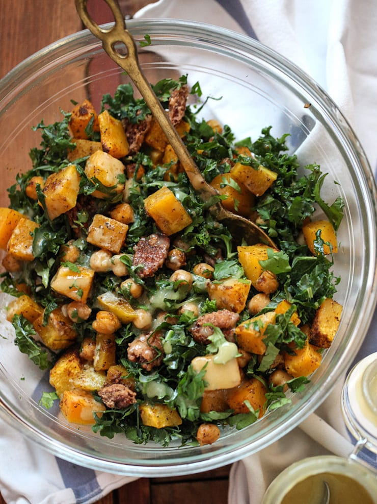 One of 15 Delicious Fall Salads - Overhead photo of a glass bowl of Kale Salad with Butternut Squash, Chickpeas and Tahini Dressing on a wood table.