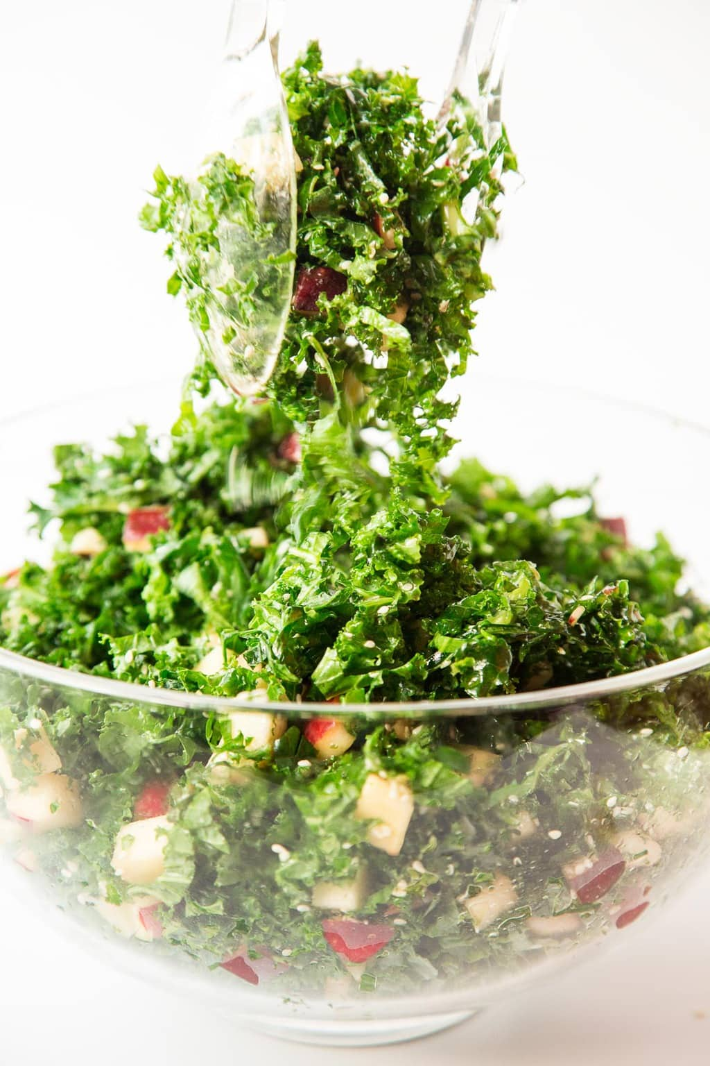 Vertical picture of Kale and Apple Salad in a glass bowl with two clear tongs tossing the salad.