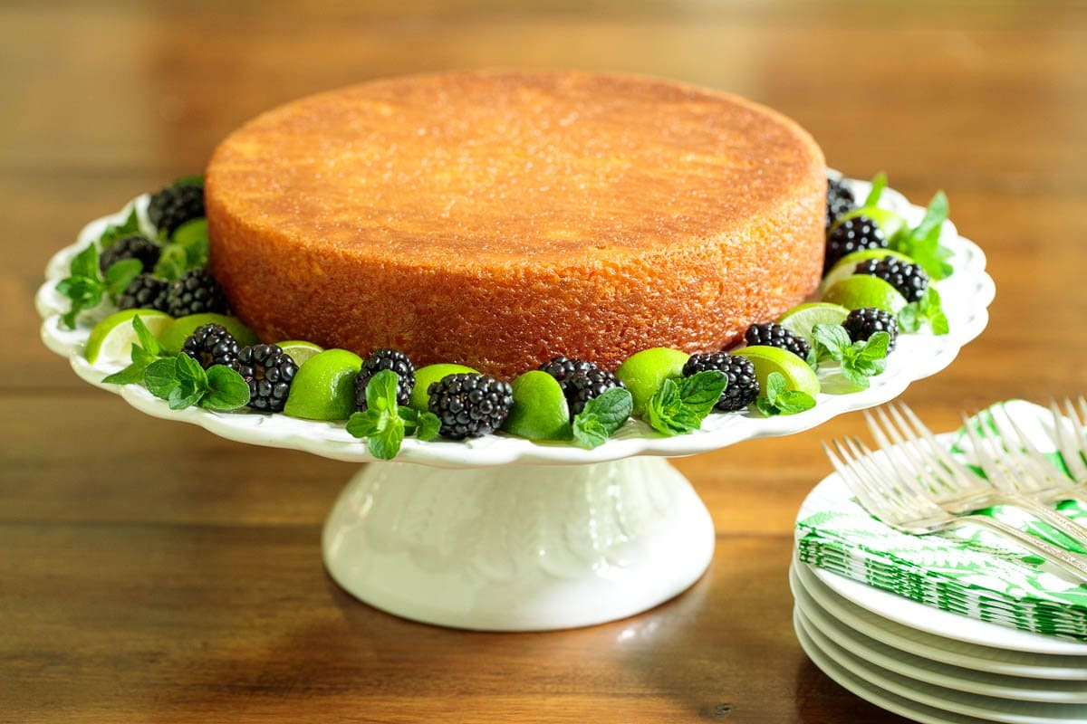 Photo of an Easy Key Lime Coconut Cake on a white pedestal cake stand, surrounded by blackberries and lime wedges on a wood table.