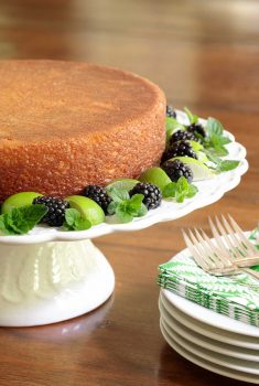 Vertical picture of key lime crunch cake on a white cake stand garnished with key limes, mint and blackberries