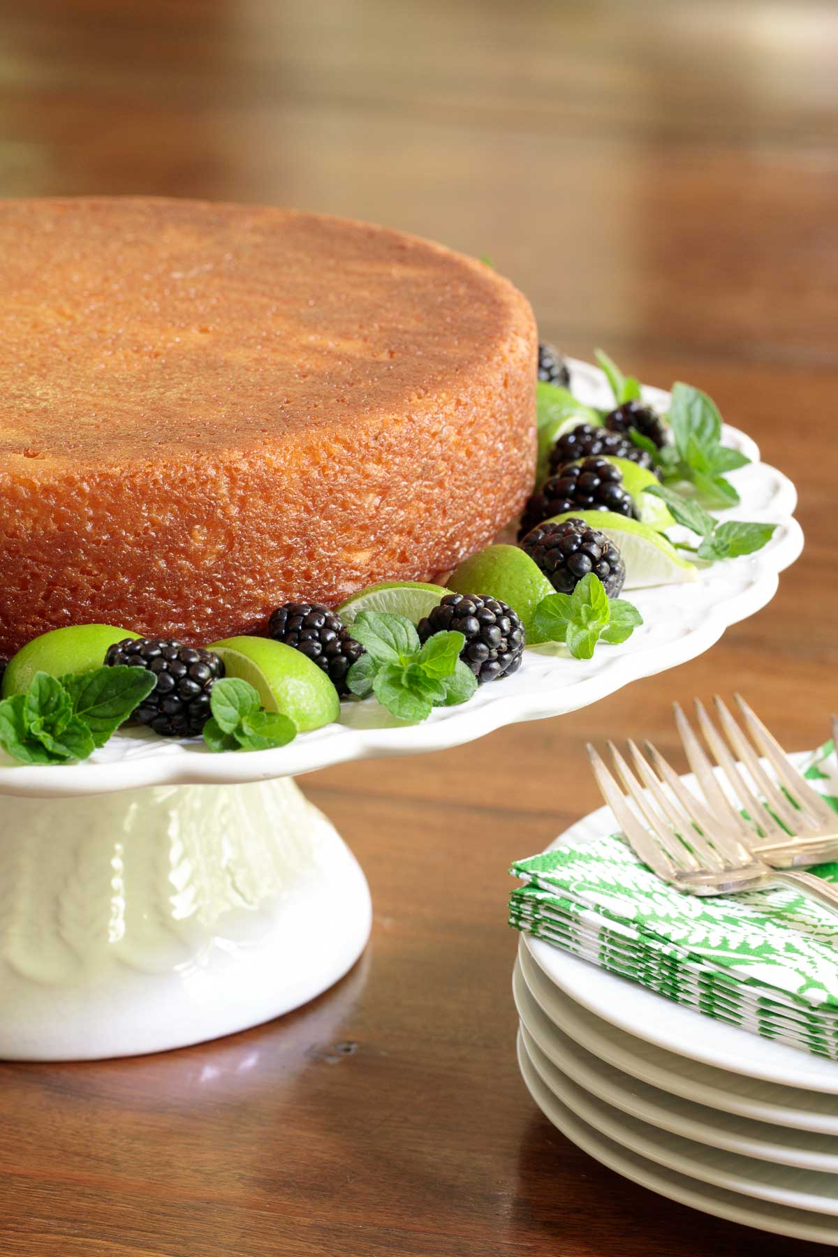 Vertical photo of a Key Lime Coconut Cake on a white pedestal cake stand garnished with key limes, mint and blackberries.