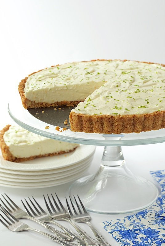 Vertical photo of a Key Lime Crunch Tart on a glass pedestal cake stand.
