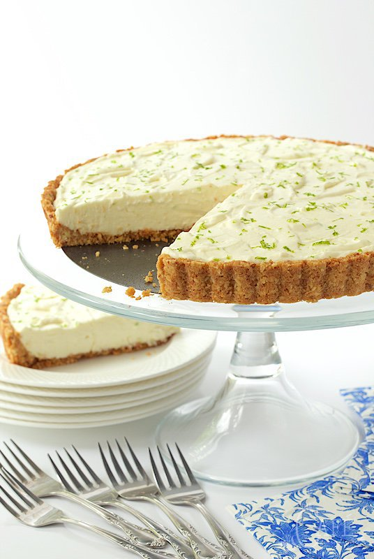 Horizontal photo of a Key Lime Crunch Tart on a glass cake pedestal with serving plates and supplies below.