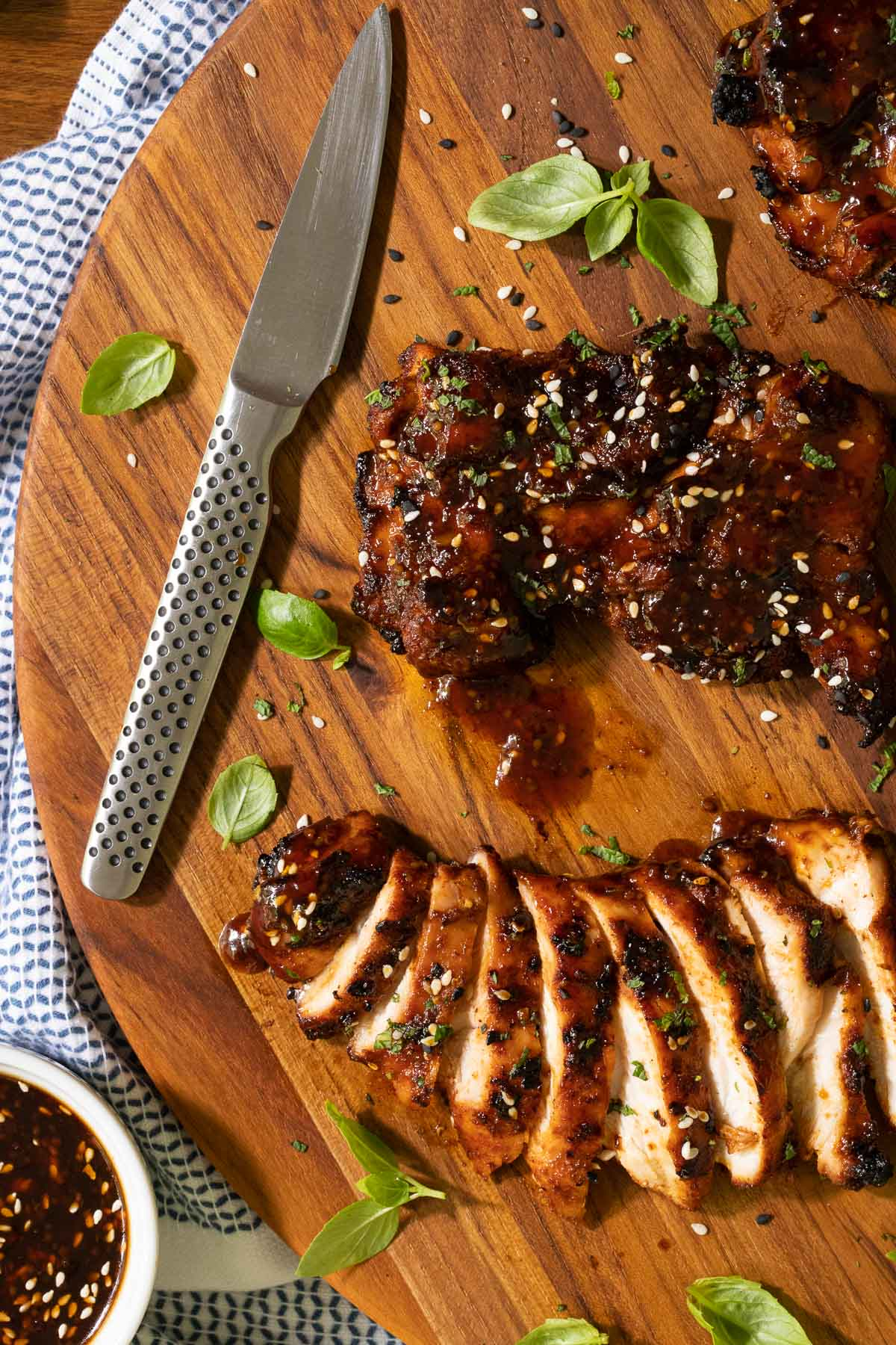 Overhead vertical closeup photo of Korean Honey Sesame Grilled Chicken on a wood cutting board.