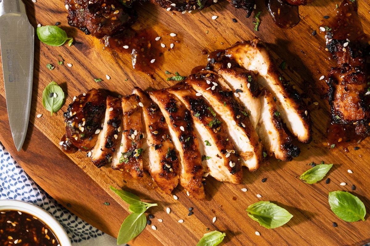 Overhead horizontal closeup photo of Korean Honey Sesame Grilled Chicken sliced and on a wood cutting board.