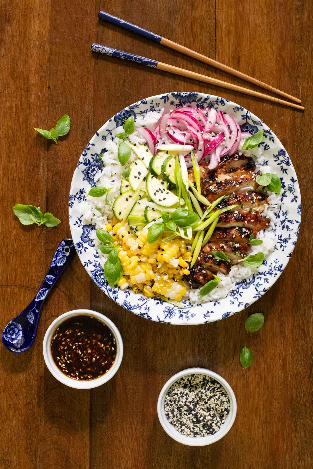 Overhead vertical photo of Korean Honey Sesame Grilled Chicken in a rice bowl with steamed fresh corn, cucumbers, pickled red onions, scallions and fresh basil.