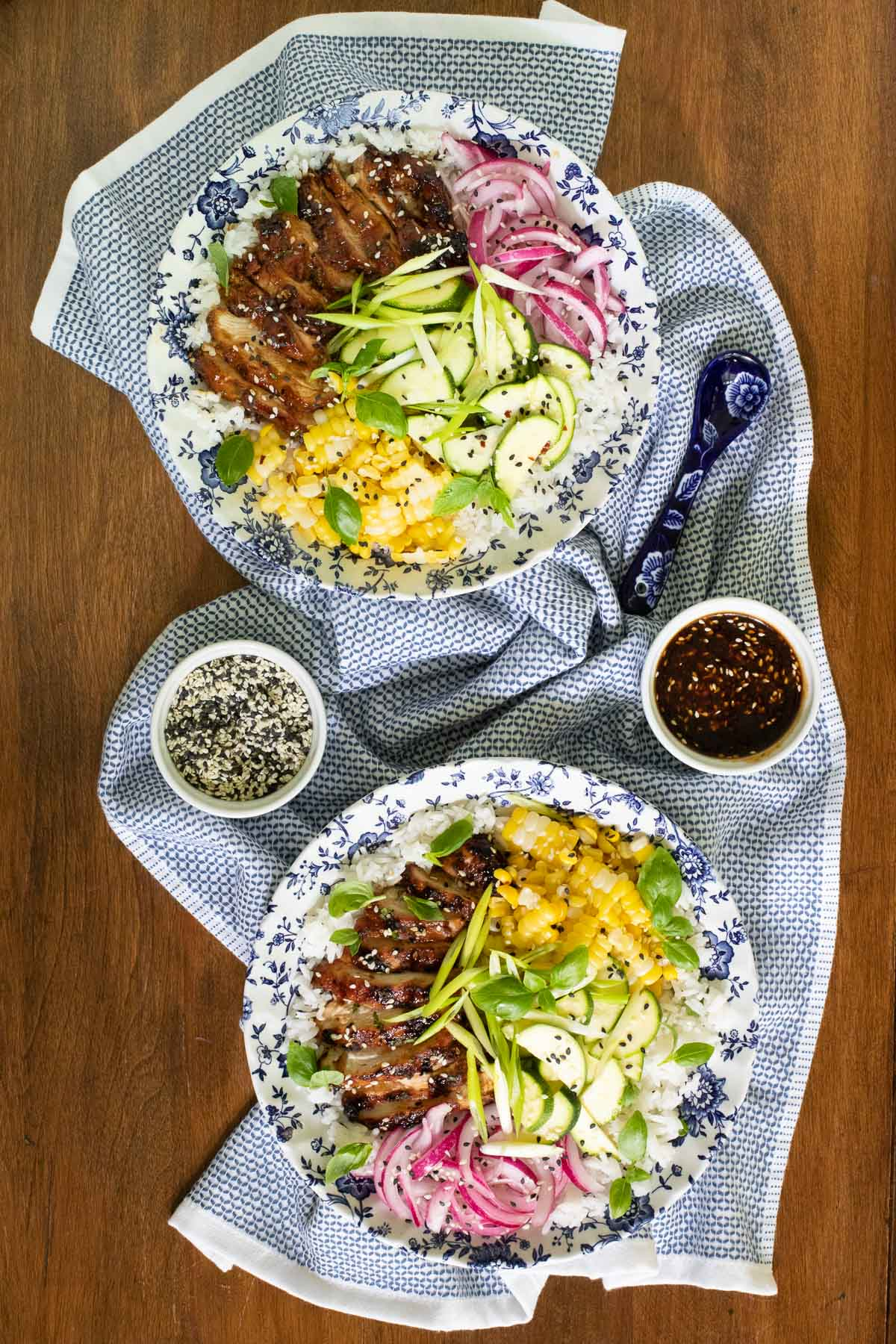 Overhead vertical photo of two serving bowls featuring Korean Honey Sesame Grilled Chicken with pickled red onions, fresh corn and basil and other veggies on a bed of rice.