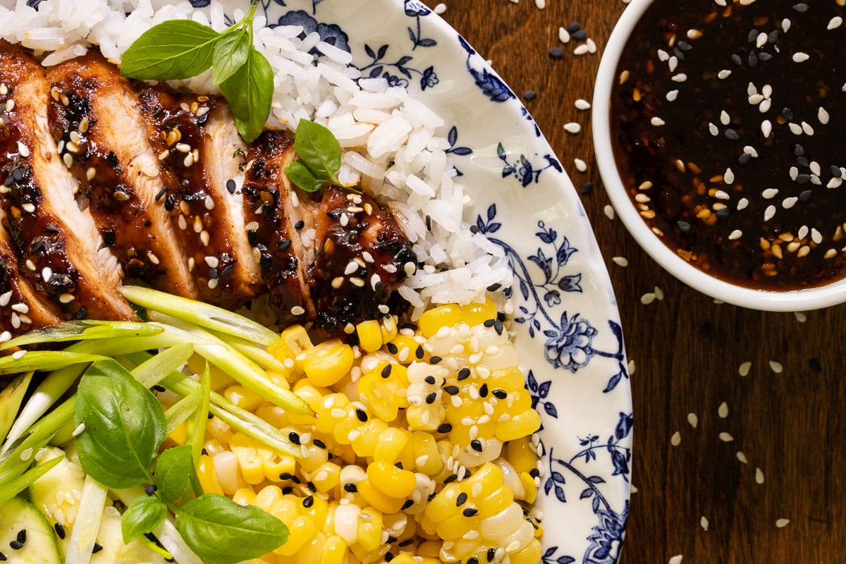 Overhead horizontal closeup photo of a rice bowl featuring Korean Honey Sesame Grilled Chicken with steamed fresh corn, scallions, sesame seeds, cucumbers and basil leaves.
