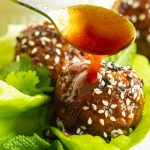 Close up vertical photo of Korean Meatball Lettuce Wraps with sauce being drizzled on top.