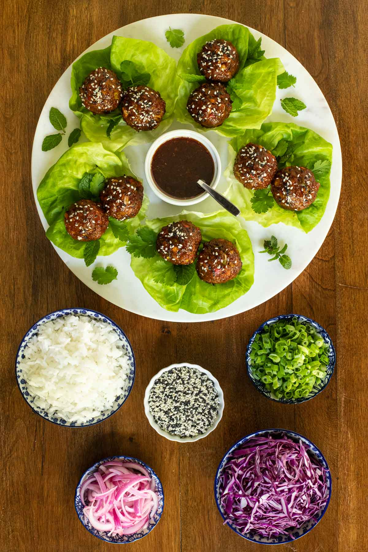 Overhead vertical photo of a platter of Korean Meatball Lettuce Wraps with bowls of the individual foods that go in the wraps including, pickled onions, rice, scallions, shredded purple cabbage and seeds.
