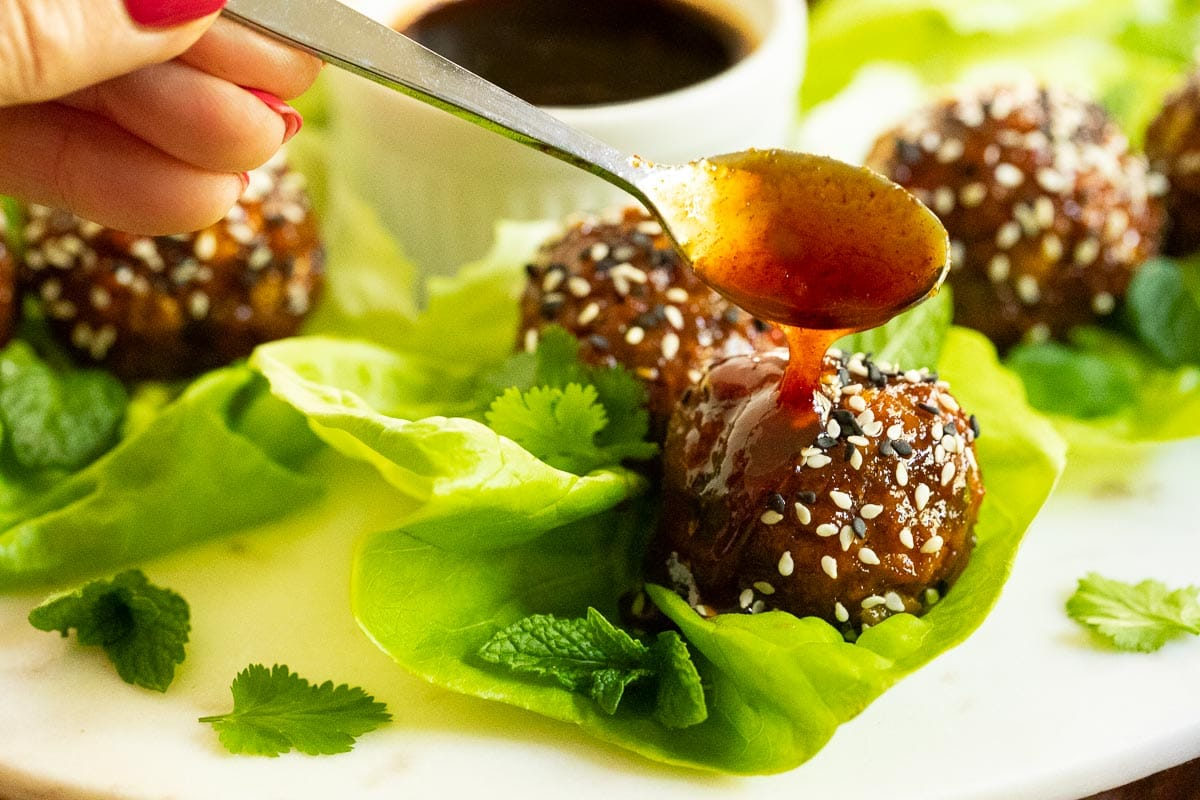 Horizontal photo of a person spooning Korean glaze/sauce over Korean Meatball Lettuce Wraps.