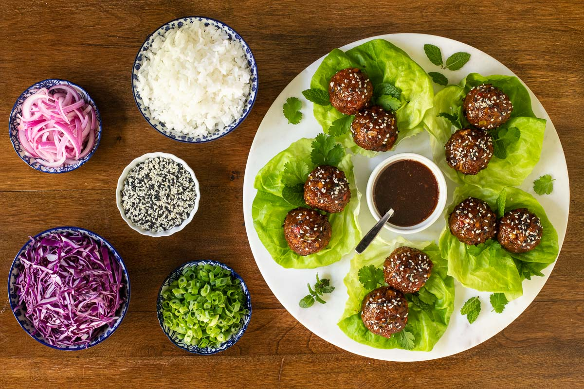 Overhead horizontal photo of a plate of Korean Meatball Lettuce Wraps surrounded by bowls of garnishes, rice and tuxedo sesame seeds.
