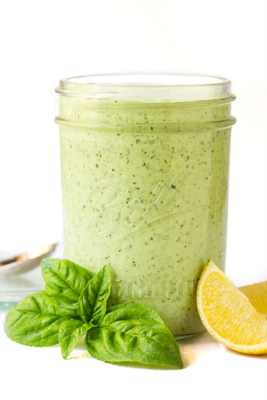 Vertical closeup photo of a Ball glass jar filled with Lemon Basil Buttermilk Dressing with fresh basil leaves and lemon wedges in the foreground.