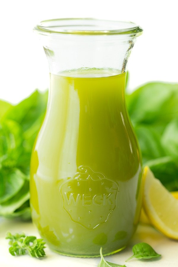 Vertical photo of Lemon Basil Oil in a glass jar with fresh basil and lemons in the background.