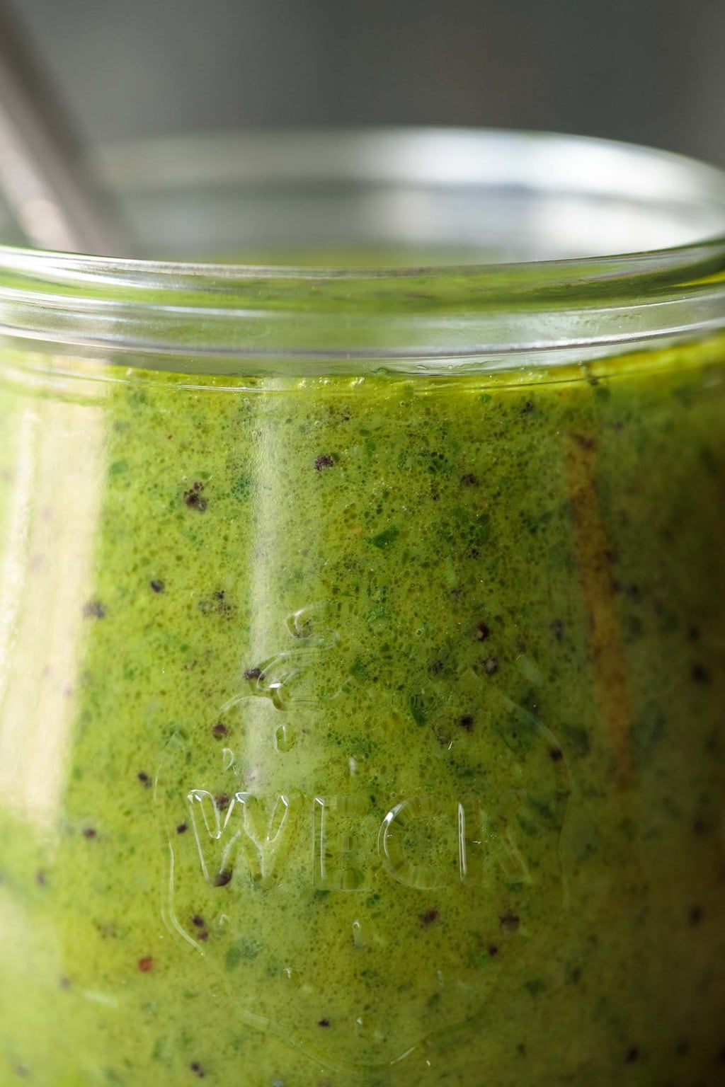 Closeup photo of a glass jar of Lemon Basil Poppy Seed Dressing.