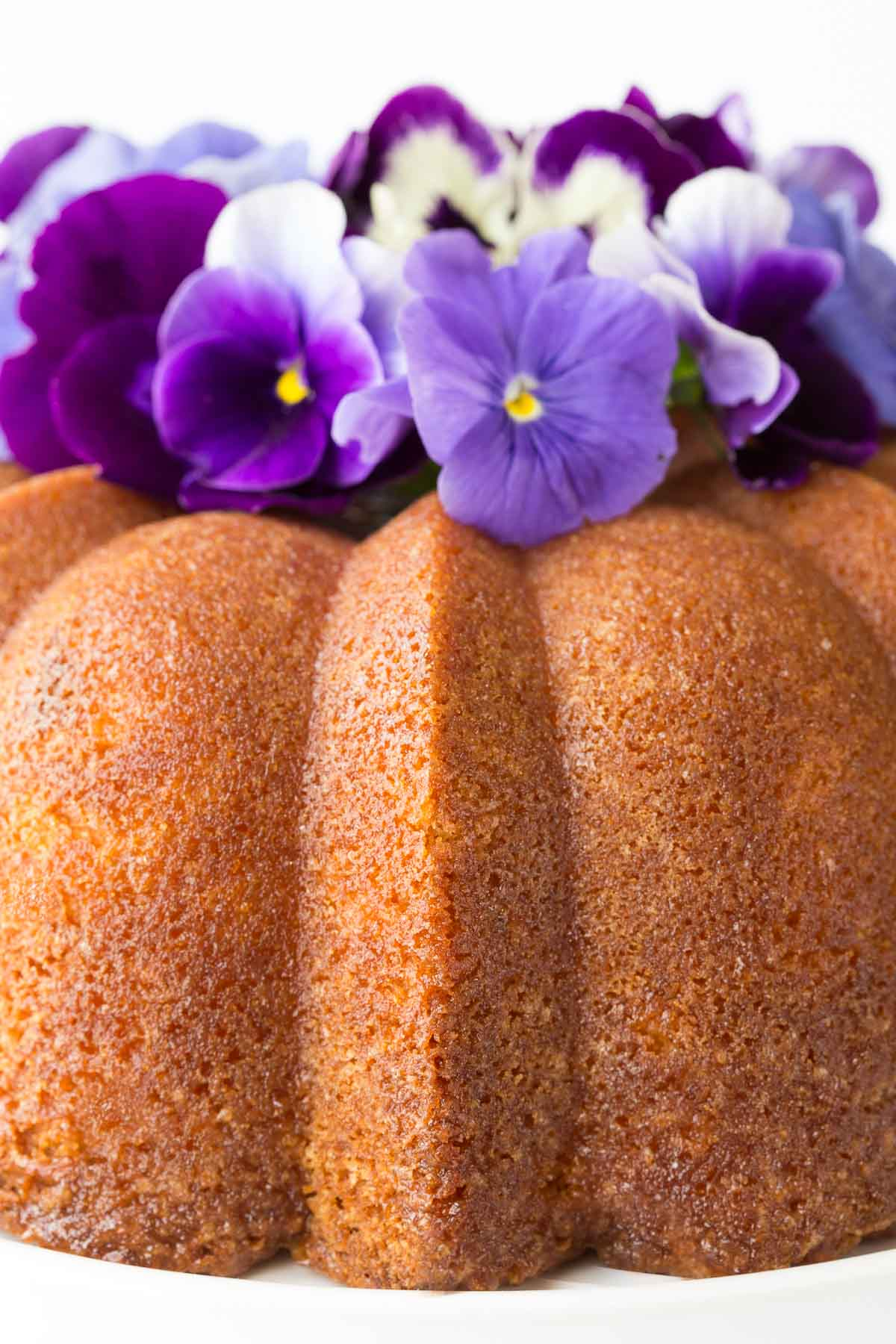 Closeup photo of the side of a Lemon Buttermilk Pound Cake with purple and white pansies on top as decoration.
