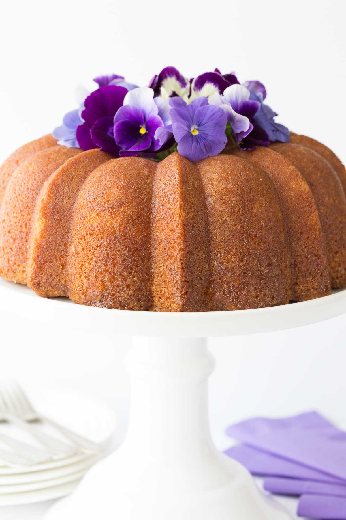 Vertical photo of a Lemon Buttermilk Pound Cake on a white cake stand.
