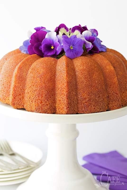 Vertical closeup photo of Lemon Buttermilk Pound Cake on a white pedestal cake stand decorated with purple pansies.