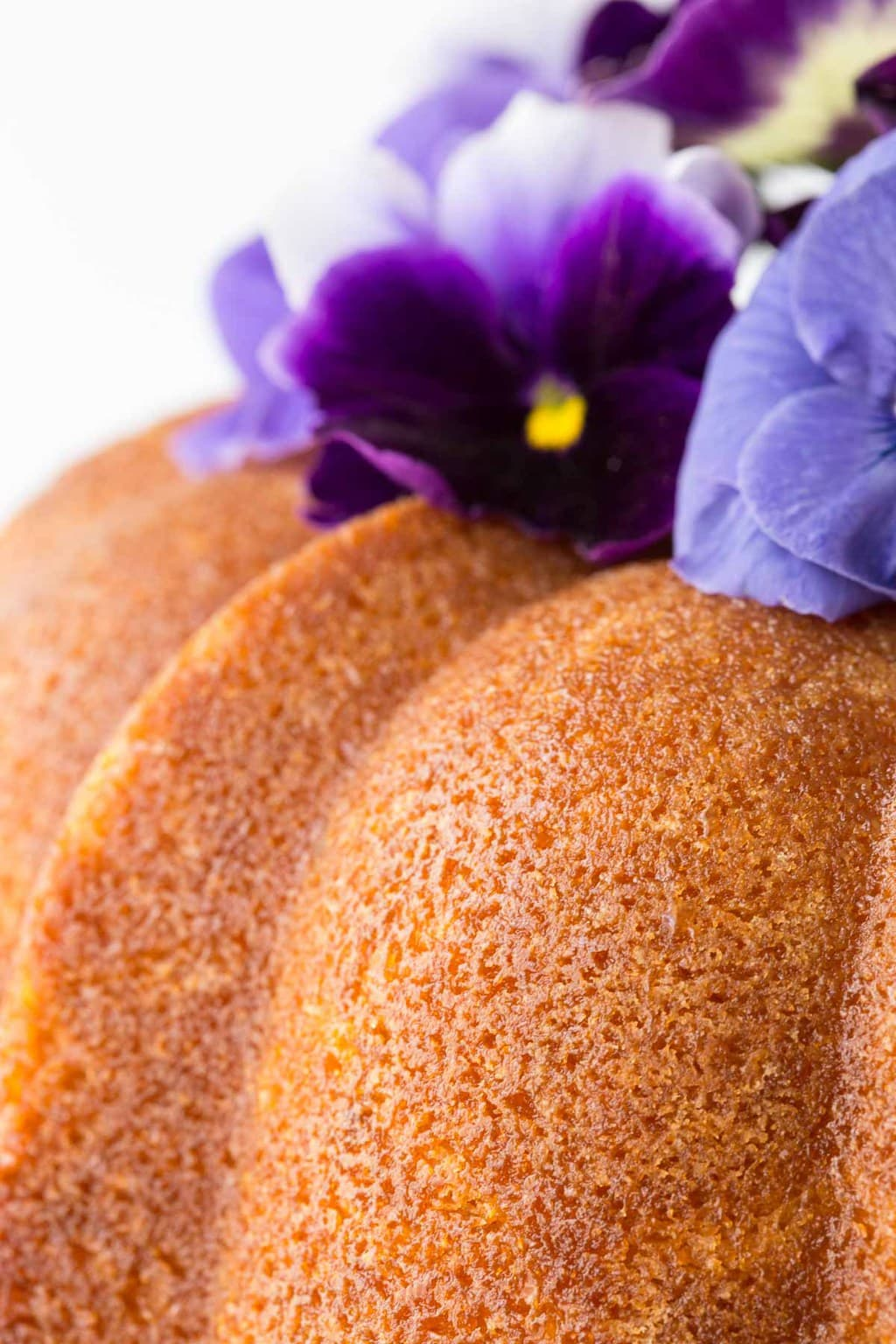 Closeup photo of the side of a Lemon Buttermilk Pound Cake with purple pansies on top.