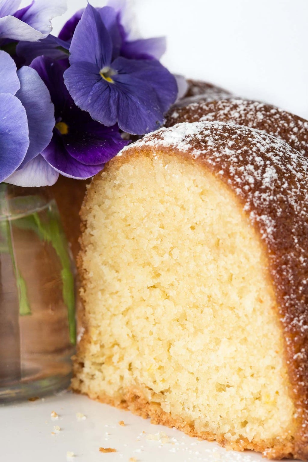 Closeup photo of the side of a Lemon Buttermilk Pound Cake with a glass jar with pansies in the center of the cake.