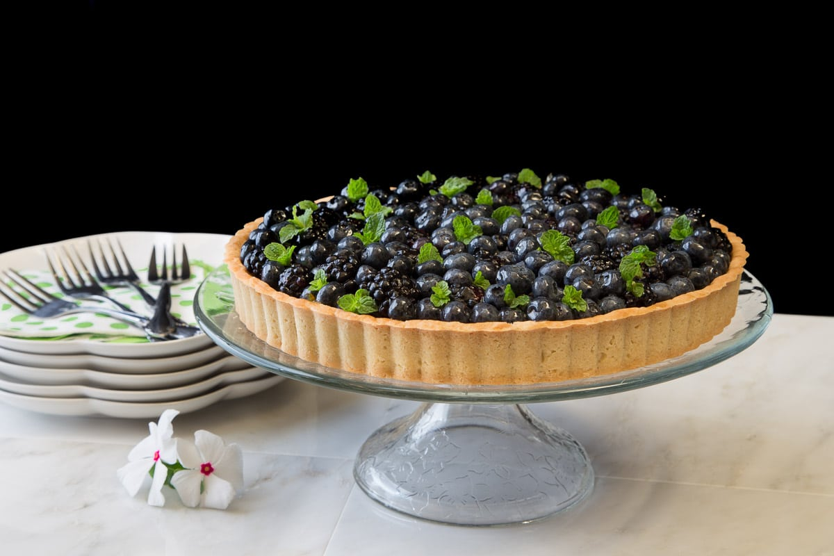 Horizontal photo of a Lemon Cheesecake with Glazed Berries with serving dishes and utensils in the background.